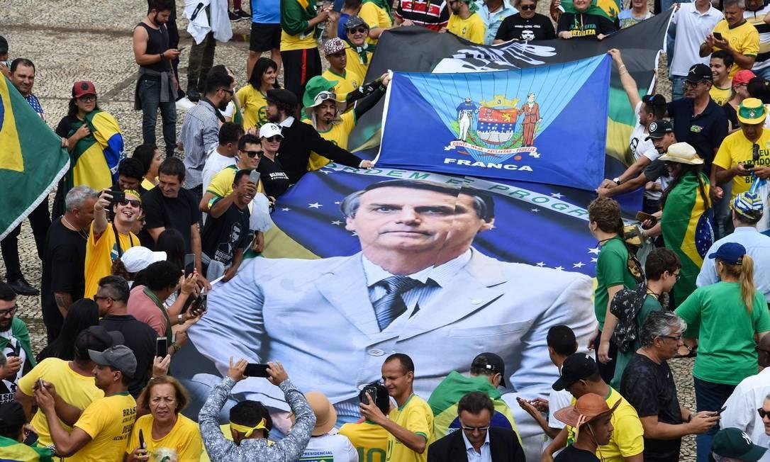 Cartaz com a foto de Bolsonaro é carregado por apoiadores que foram assistir à posse em Brasília Foto: EVARISTO SA / AFP