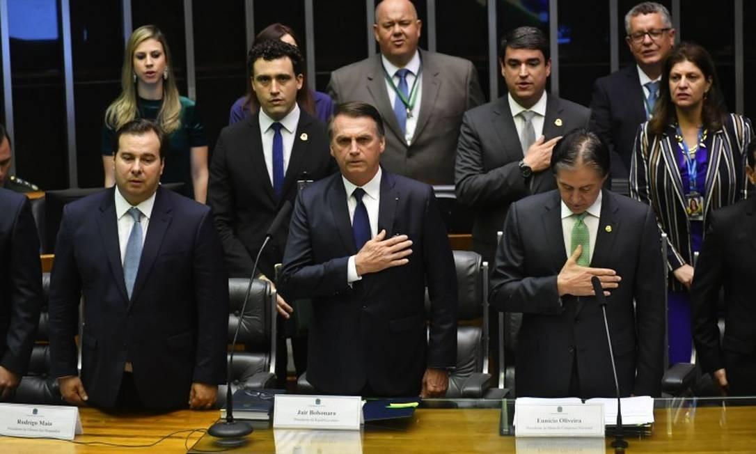 Bolsonaro ao lado do presidente do Senado, Eunício Oliveira, e do presidente da Câmara dos Deputados, Rodrigo Maia, durante a execução do Hino Nacional Foto: NELSON ALMEIDA / AFP