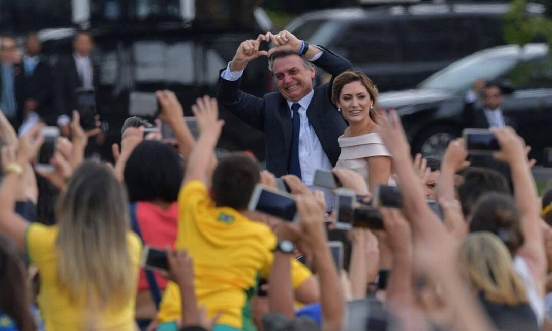Jair Bolsonaro faz símbolo de coração com as mãos na direção de eleitores ao chegar no Congresso Nacional Foto: CARL DE SOUZA / AFP