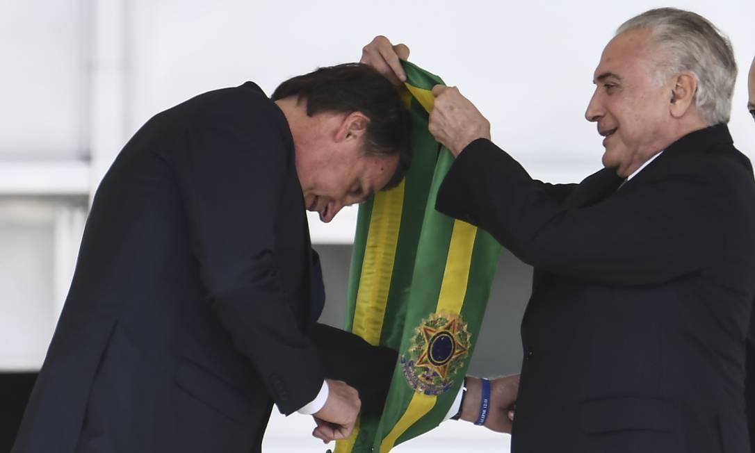Presidente Jair Bolsonaro recebe a faixa presidencial do ex-presidente Michel Temer Foto: EVARISTO SA / AFP
