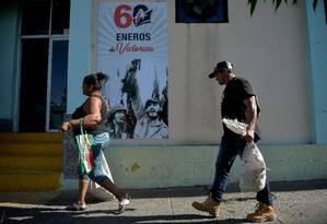 Pessoas passam por pôster que celebra o marco de 60 anos da Revolução Cubana, em Santiago de Cuba Foto: YAMIL LAGE / AFP