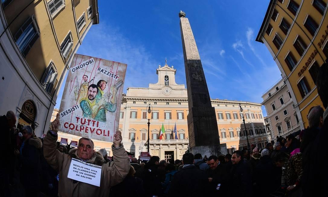 Homem segura cartaz com desenhos dos presidentes dos EUA, Donald Trump, e do Brasil, Jair Bolsonaro, e do vice-primeiro-ministro italiano Matteo Salvini, ladeados pelos dizeres 'homofóbicos, racistas e sexistas' e a frase 'todos culpados' em protesto em Roma: coalizão encabeçada pela direitista 'Liga' e o populista 'Movimento 5 Estrelas' tem seguido à risca o roteiro da guinada conservadora na liderança de diversos países do Ocidente Foto: Alberto Pizzoli/AFP/29-12-2018