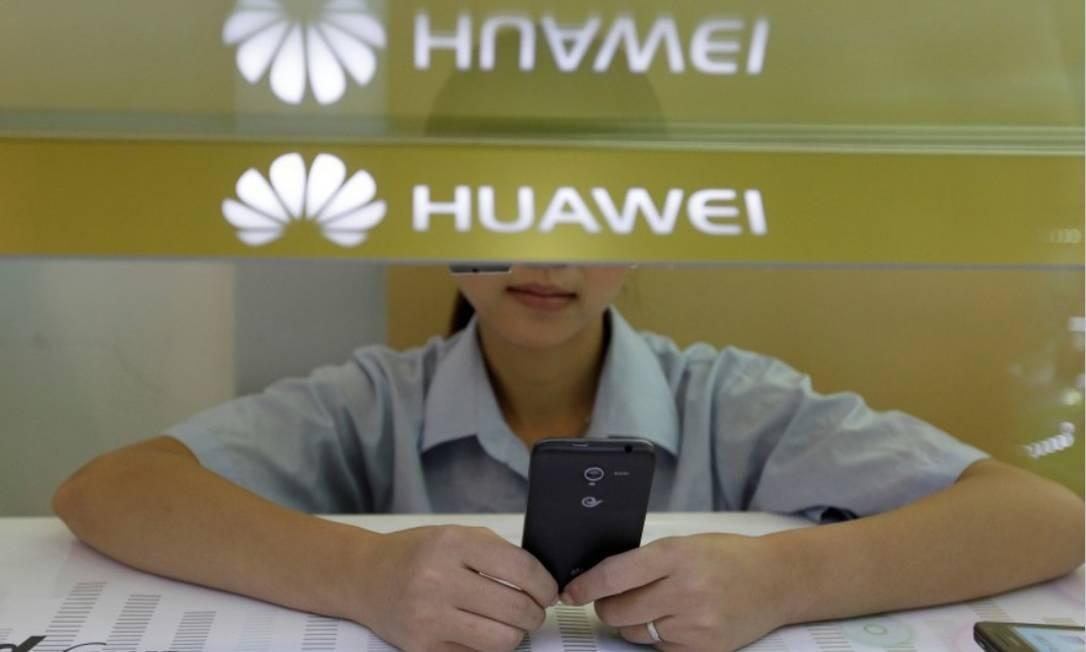 Um assistente de vendas olha para seu celular enquanto espera por clientes atrás de um balcão no estande da Huawei em Wuhan, na província de Hubei (China) Foto: Reuters