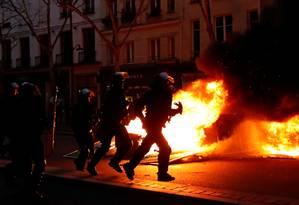 Policiais correm diante do fogo, em Paris Foto: GONZALO FUENTES / REUTERS