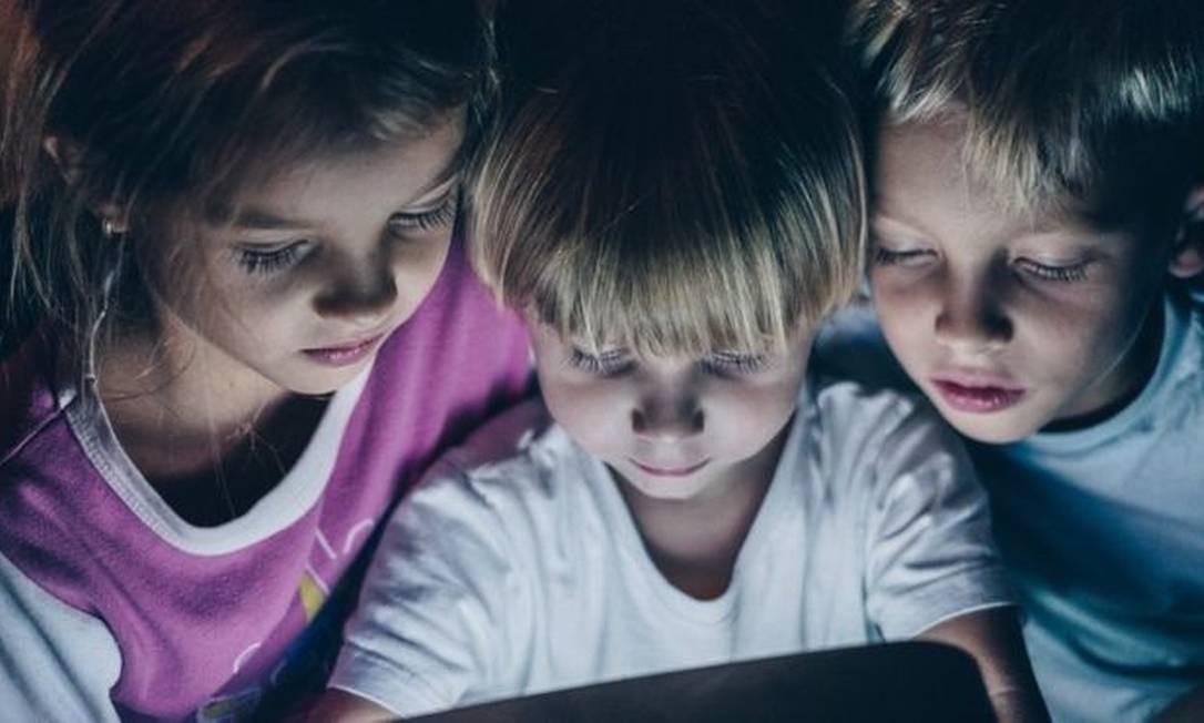 Médicos dizem em estudo que o problema não é usar, mas a quantidade de tempo que as crianças ficam nos smartphones e tablets Foto: GETTY IMAGES