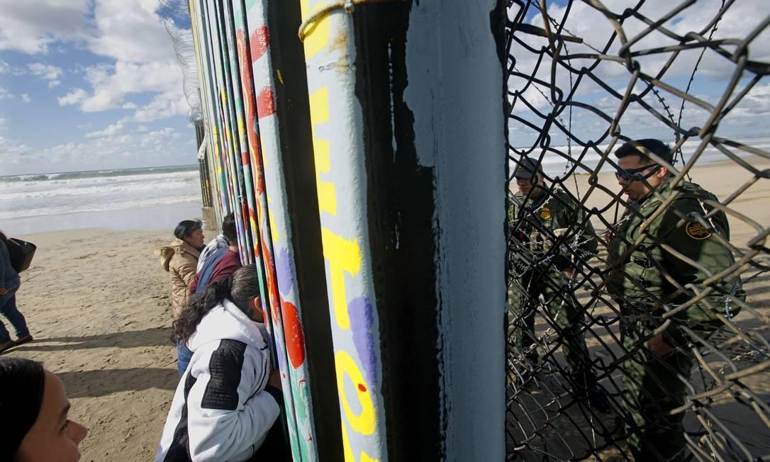 Na fronteira entre EUA e México, forças americanas de um lado; e civis não americanos de outro, em Tijuana Foto: Sandy Huffaker / AFP