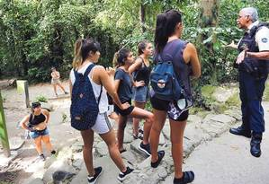 No Parque Lage, vigilante tenta convencer grupo de turistas a não entrar na mata; ICMBio diz que há esforço conjunto por maior policiamento, mas PM afirma não ser responsável pela área, que é federal Foto: Márcia Foletto / Agência O GLOBO