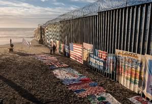 Centro-americanos observam exposição de artista Robenz em cerca na fronteira entre México e EUA, em Tijuana Foto: GUILLERMO ARIAS / AFP