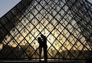 Casal se beija em frente à Pirâmide do Louvre, que chega aos 30 anos em 2019 como um símbolo de Paris Foto: LUDOVIC MARIN / AFP