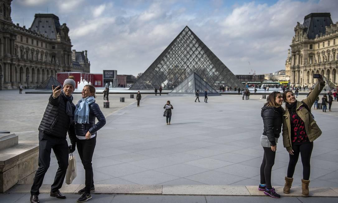 É difícil encontrar um turista que não faça questão de uma selfie com a pirâmide Foto: MARTIN BUREAU / AFP