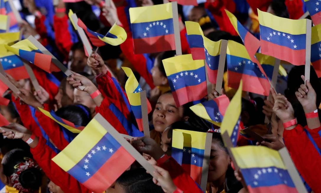 Crianças com bandeiras nacionais antes da posse cerimonial do presidente venezuelano CARLOS GARCIA RAWLINS / REUTERS