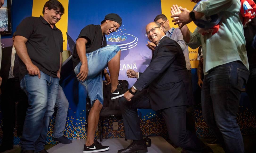 Durante homenagem a Ronaldinho Gaúcho, no Maracanã, no dia 8 de janeiro, quando o craque colocou seus pés na calçada da fama do estádio, lá estava Witzel de novo; na foto, ele finge engraxar as chuteiras do ex-jogador, comemoração comum no mundo do futebol Foto: MAURO PIMENTEL / AFP