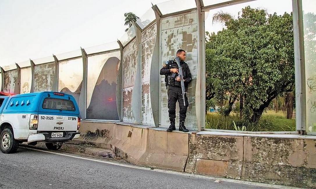 Policial com fuzil diante de uma abertura entre as placas acústicas às margens da via Foto: Guito Moreto / Agência O GLOBO