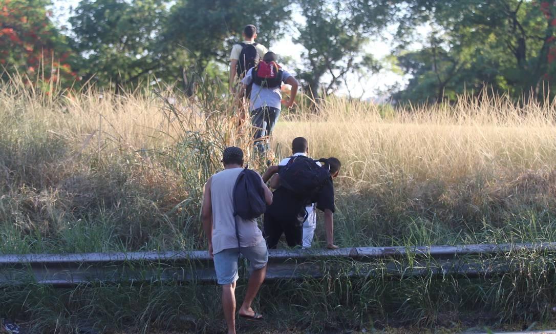 Após o acidente, passageiros saem da pista para fugir do engarrafamento Foto: Fabiano Rocha / Agência O Globo