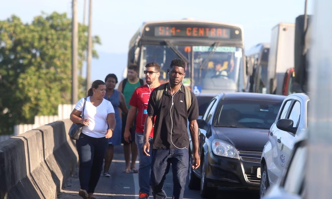Com o trânsito parado, os passageiros abandonam os ônibus para fugir do engarrafamento Foto: Fabiano Rocha / Agência O Globo