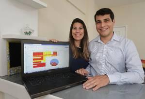 Fábio e Aline com a planilha de gastos no computador Foto: Marcio Alves / Agência O Globo