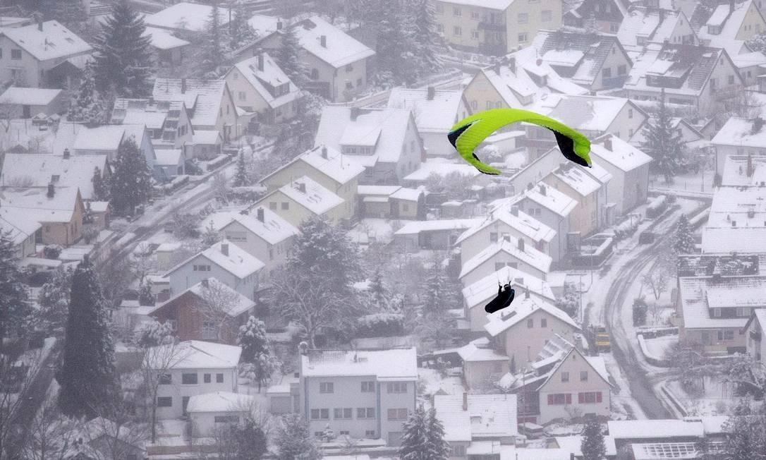Um parapente sobrevoa casas cobertas de neve na cidade de Neuffen, na Alemanha Foto: MARIJAN MURAT / AFP