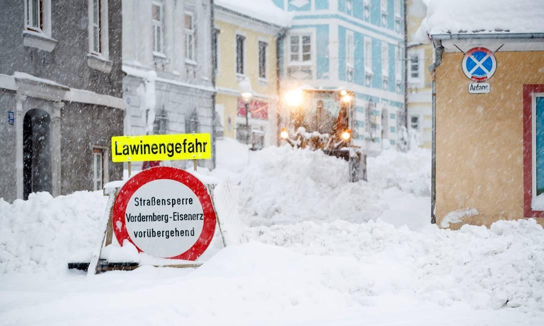 """Na cidade de Vordernberg, placa coberta de neve alerta """"Perigo de Avalanches"""" ERWIN SCHERIAU / AFP"""