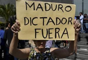 Manifestante carrega cartaz contra o presidente venezuelano, Nicolás Maduro, durante protesto em Caracas Foto: YURI CORTEZ / AFP