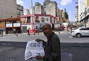 Um homem lê um jornal em uma rua de Caracas Foto: YURI CORTEZ / AFP