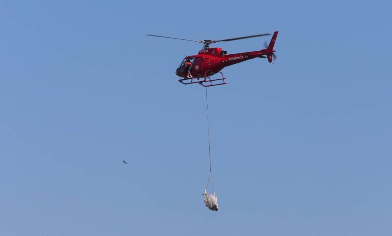 Vítima do acidente com helicóptero é resgatada pelos bombeiros em uma rede Foto: Fabiano Rocha / Agência O Globo