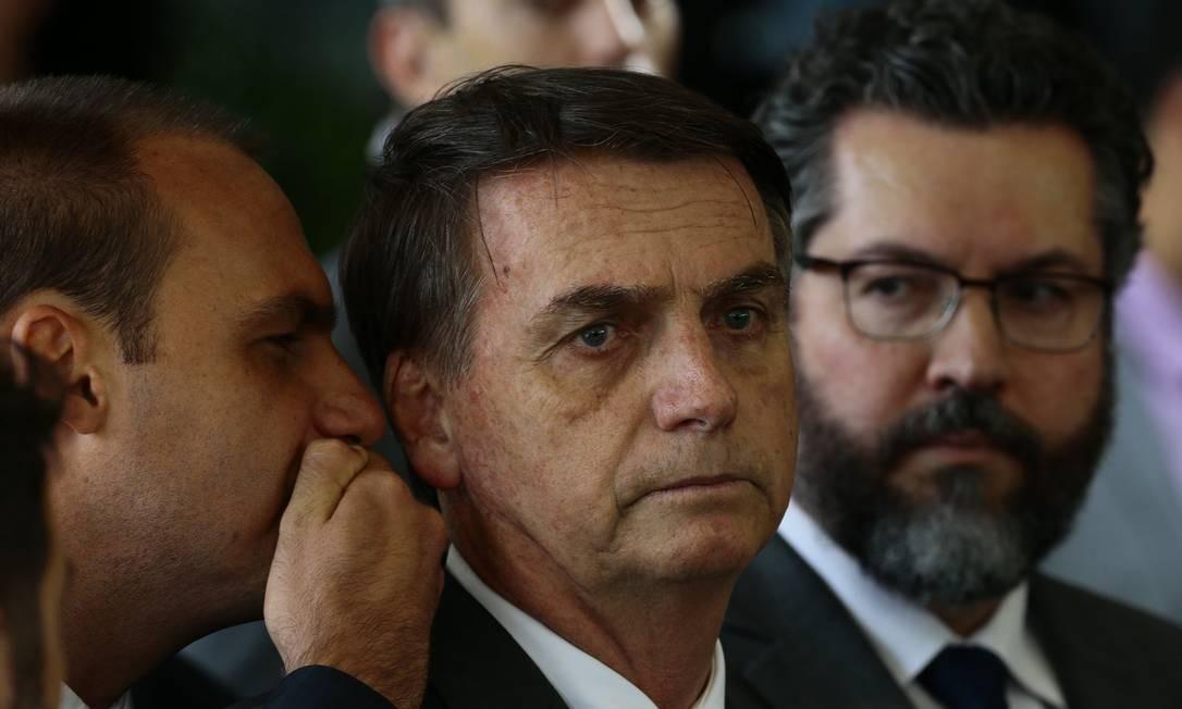 Deputado Eduardo Bolsonaro fala ao ouvido do pai, o presidente Jair Bolsonaro, durante anúncio do chanceler Ernesto Araújo Foto: Jorge William / Agência O Globo