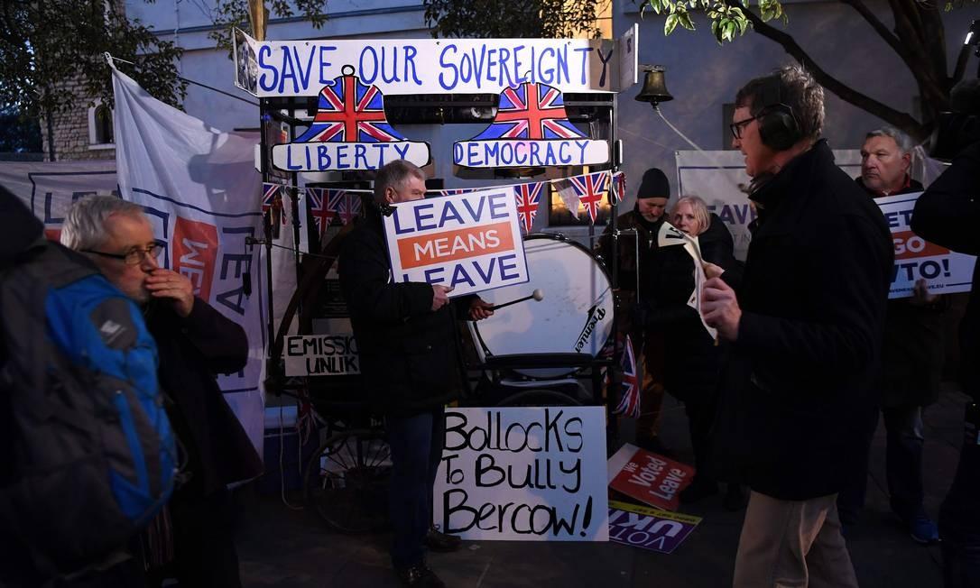 """Ativistas anti-UE seguravam cartaz de """"sair significa sair"""" do lado de fora do Parlamento no centro de Londres; eles defendiam a aprovação do acordo da primeira ministra Theresa May, negociado com a União Europeia Foto: PAUL ELLIS / AFP"""