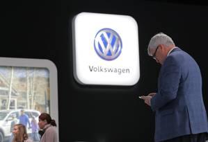 Homem usa celular durante conferência para anunciar a aliança Ford/Volkswagen em Detroit, EUA Foto: BRENDAN MCDERMID / REUTERS