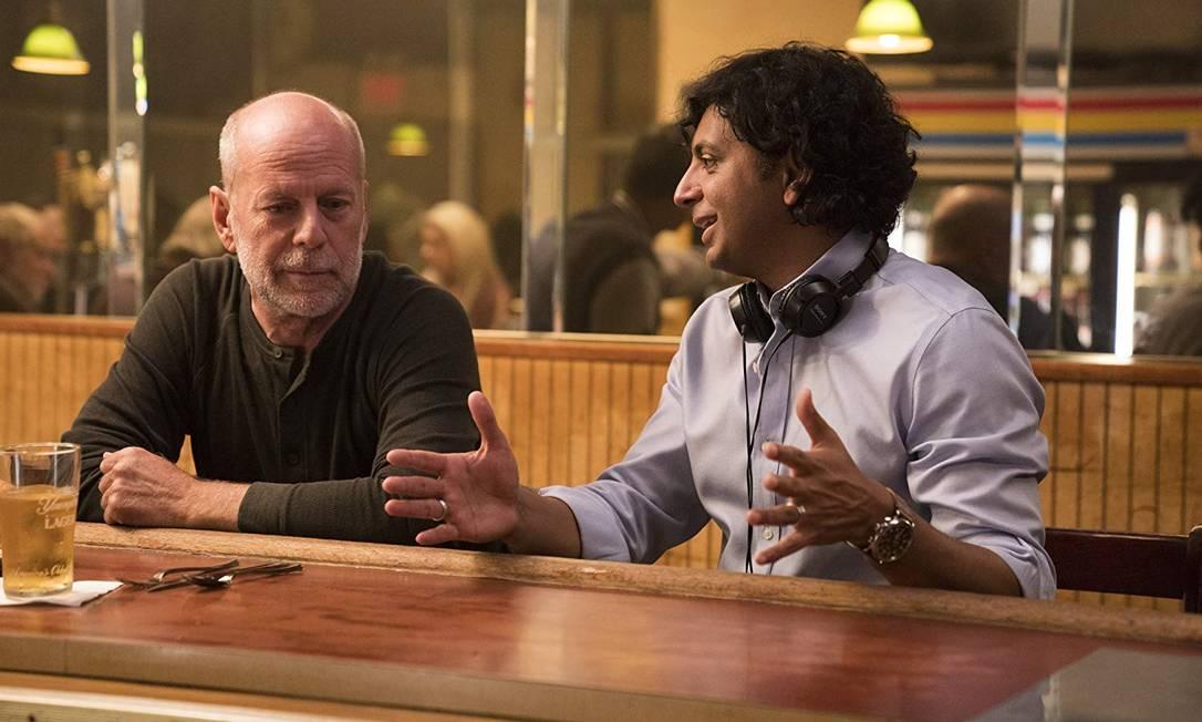 Bruce Willis recebe instruções de M. Night Shyamalan em um dos cenários de 'Vidro' Foto: Divulgação