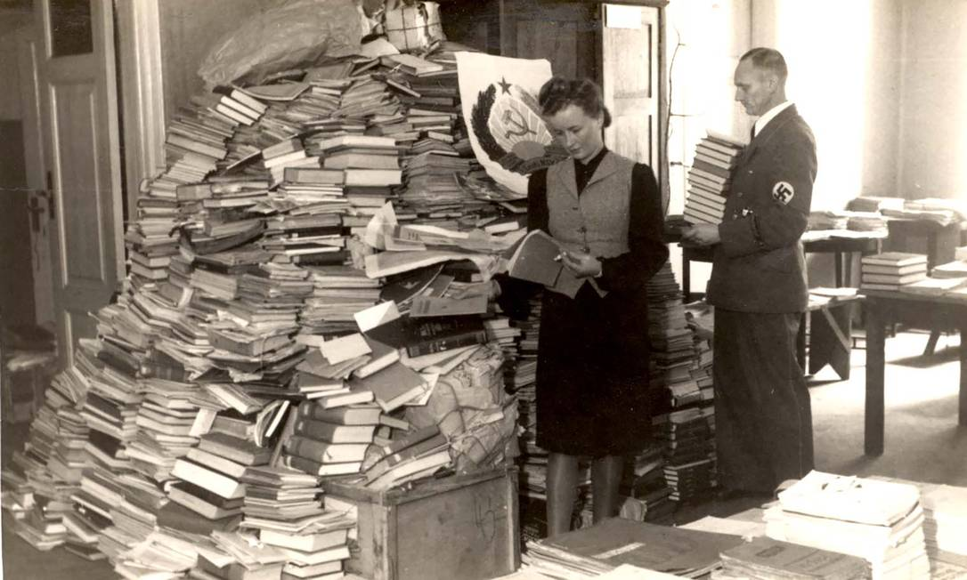 Membros da força-tarefa liderada pelo nazista Alfred Rosenberg, que saqueou mais de 6 mil bibliotecas, examinam livros na Estônia na época da guerra Foto: YAD VASHEM PHOTO ARCHIVES/NYT / NYT