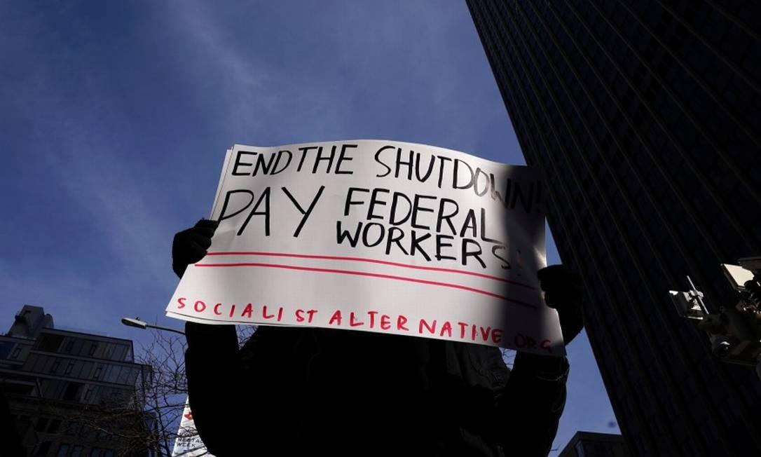 Trabalhador segura cartaz contra shutdown: