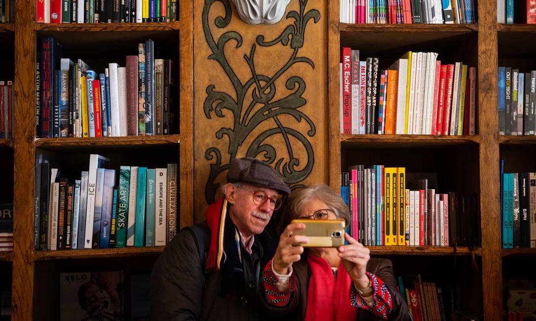 Um casal posa em frente a um detalhe decorativo no interior da Livraria Lello Foto: MIGUEL RIOPA / AFP