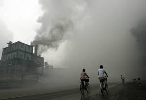 Ciclistas passam por uma fábrica em Yutian, a 100 km de Pequim: poluição atmosférica aumenta incidência de doenças respiratórias Foto: Peter Parks / AFP/18-7-2006