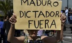 """""""Fora Maduro ditador"""" diz cartaz de manifestante em Caracas Foto: YURI CORTEZ / AFP"""
