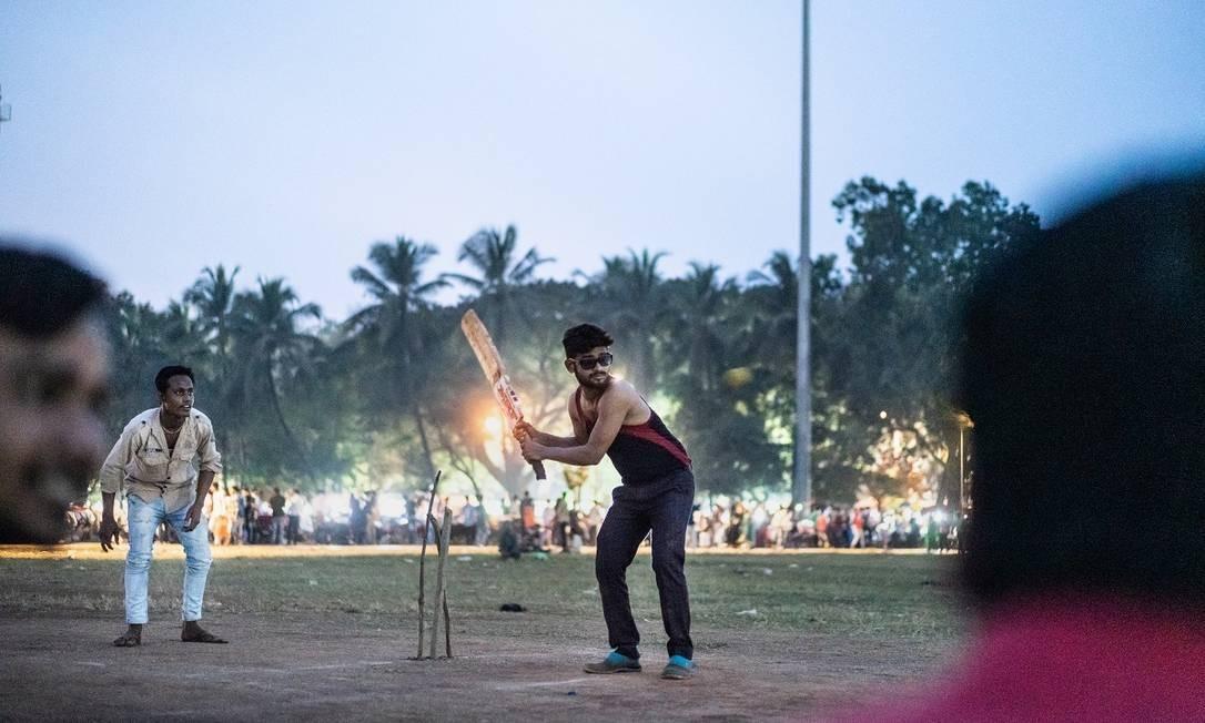 Jovens jogam críquete em um parque nos arredores da Fashion Street, em Mumbai, na Índia Foto: Philippe Calia / The New York Times