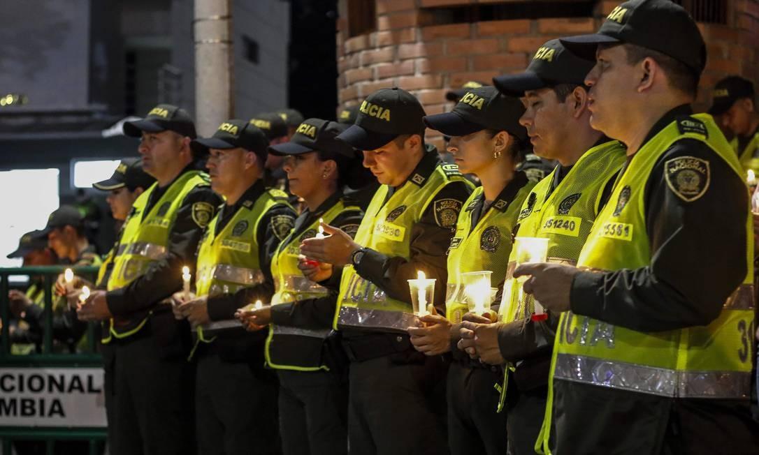 Membros da Polícia Nacional seguram velas em homenagem a colegas mortos em ataque Foto: SCHNEYDER MENDOZA / AFP