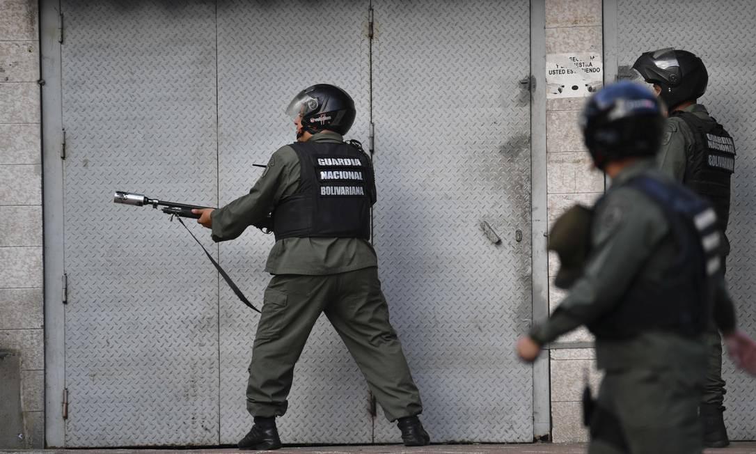 Oficiais da Guarda Nacional Bolivariana lançam gás lacrimogêneo contra manifestantes após rebelião de militares Foto: YURI CORTEZ / AFP