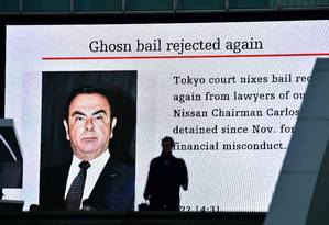 Pedestre passa por um painel elétrico mostrando a notícia de que o tribunal rejeitou o novo pedido de fiança a Crlos Ghosn Foto: KAZUHIRO NOGI / AFP