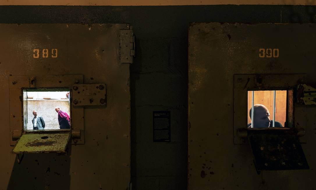 """Vídeos são vistos através das janelas das portas da prisão em exibição no """"KGB Spy Museum"""", em Nova York Foto: KARSTEN MORAN / NYT"""