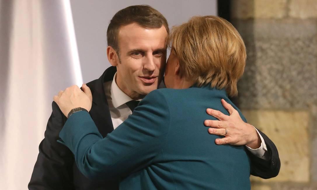 Presidente francês, Emmanuel Macron, e chanceler alemã, Angela Merkel, se abraçam durante cerimônia de assinatura de tratado de cooperação Foto: LUDOVIC MARIN / AFP