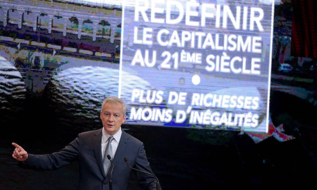 """Le Maire discursa: na tela atrás do ministro, está escrito """"Redefnir o capitalismo no século XXI. Mais riquezas, menos desigualdades"""" Foto: ERIC PIERMONT / AFP"""
