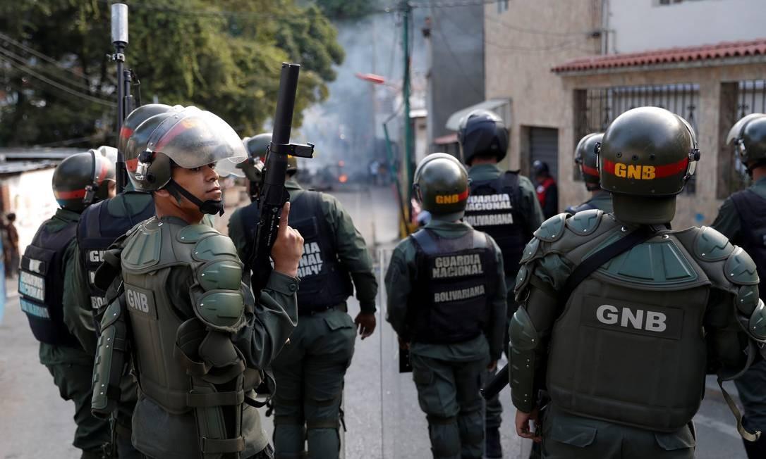 Agentes da Guarda Nacional Bolivariana perto de manifestantes em Caradas no dia 21 de janeiro de 2019 Foto: Carlos Garcia Rawlins / REUTERS