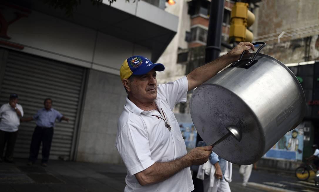 Venezuelano bate em panela em sinal de oposição ao governo Maduro; madrugada desde 23 de janeiro, data histórica na Venezuela, teve horas de panelaço Foto: FEDERICO PARRA / AFP