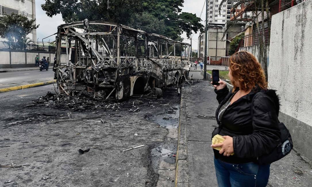 Mulher tira foto de um ônibus queimado em Caracas na véspera de jornada de marchas convocada pela oposição venezuelana Foto: LUIS ROBAYO / AFP