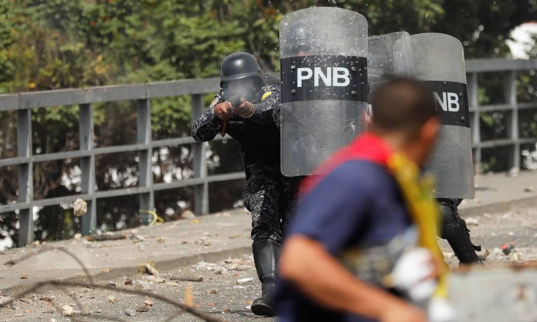 Agente da Polícia Nacional dispara bala de borracha contra manifestante em Caracas Foto: Manaure Quintero / REUTERS