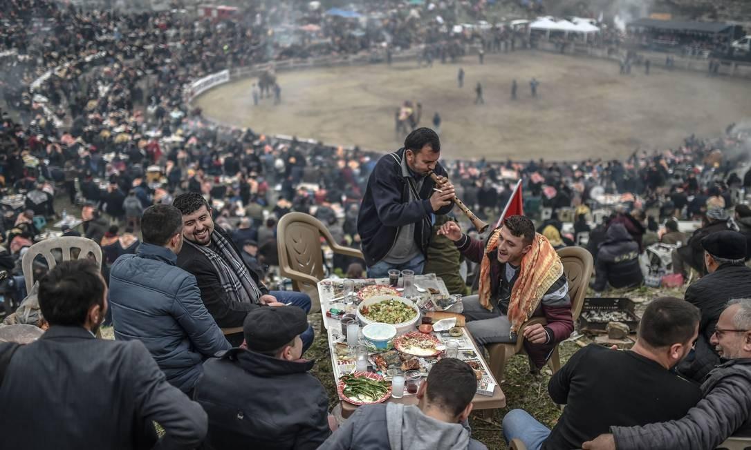 Pessoas participam de uma refeição durante o festival Selcuk Camel Foto: BULENT KILIC / AFP
