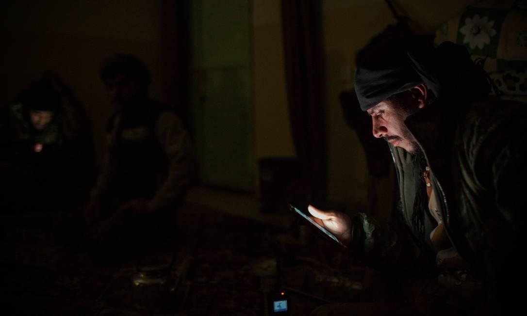O comandante curdo Haval Amir acompanha pelo celular a movimentação no campo de batalha enquanto dá instruções pelo rádio a seus soldados que avançam sobre posições do Estado Islâmico em uma noite da segunda semana de janeiro Foto: Yan Boechat / .
