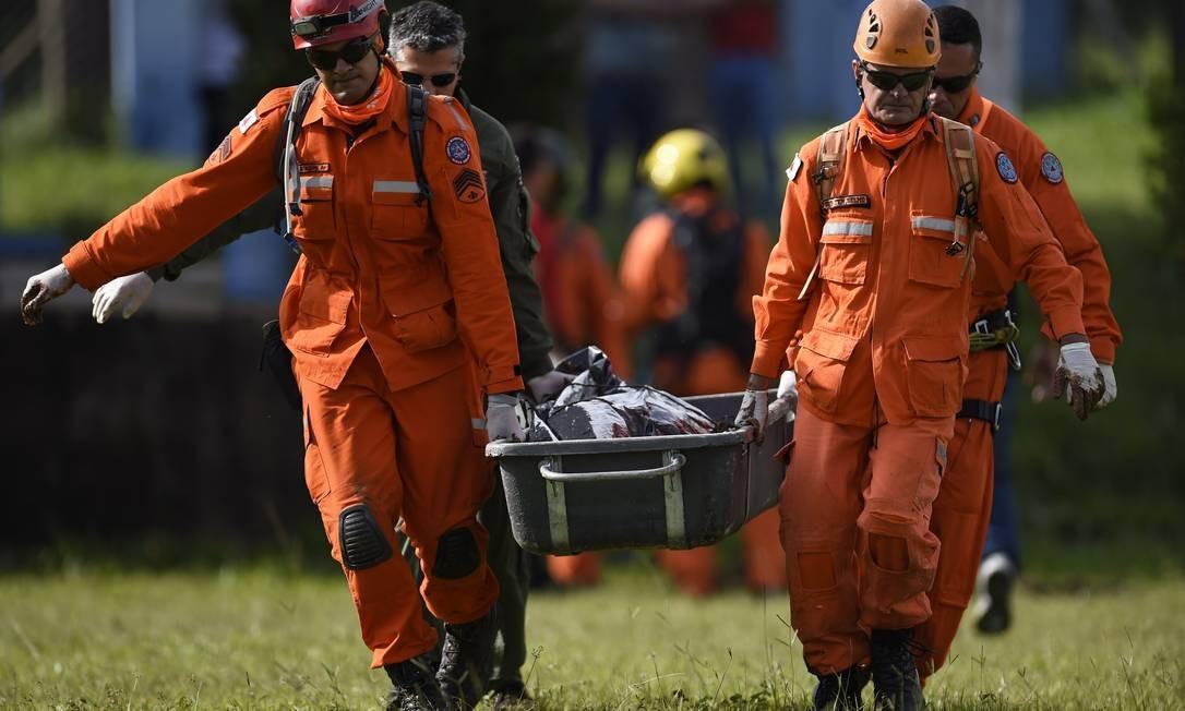 Bombeiros militares transportam o cadáver de uma vítima recuperada da lama Foto: DOUGLAS MAGNO / AFP