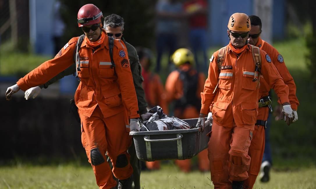 Bombeiros carregam o corpo de uma das vítimas da tragédia Foto: Douglas Magno / AFP