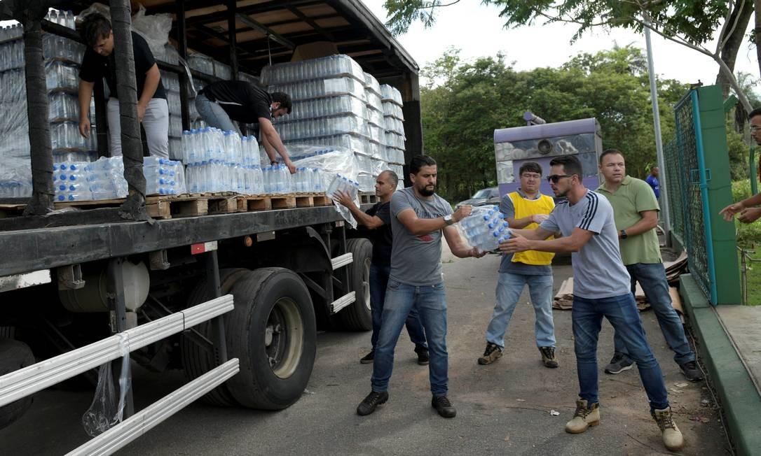 Voluntários retiram de um caminhão garrafas de água mineral enviadas às pessoas afetadas pela tragédia em Brumadinho WASHINGTON ALVES / REUTERS